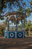 Close-up of an old colorful gazebo in the middle of verdant garden full of trees, in a sunny day at São Manuel. royalty free stock photos