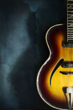 Close-up of old electric jazz guitar on a dark blue background. With copy space royalty free stock photography