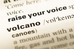 Close up of old English dictionary page with word raise your voice stock photography
