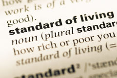 Close up of old English dictionary page with word standard of living stock images