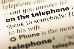 Close up of old English dictionary page with word on the telephone stock photography