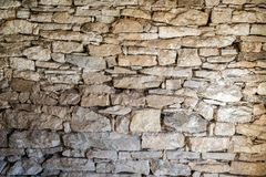 Close up of old flat brown and gray stone wall texture. Layered rocks on a house or building. Architectural stone wall exterior. Typical in Bulgaria royalty free stock photo