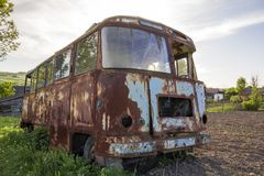 Close-up of old forsaken passenger bus with broken windows rusting in high green weedy grass on edge of plowed brown field on stock photo