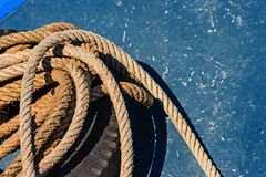 Close-up the old frayed boat rope on blue texture background. At Chalong pier, Phuket Thailand royalty free stock photos
