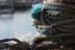 Close up of old, frayed rope tethering fishing boat to mooring in the harbor stock images