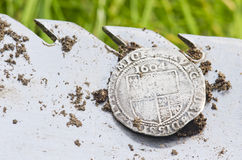Close- up on old, hammered silver coin exposed on a shovel ,found in life dig by metal detector. Stock Photos