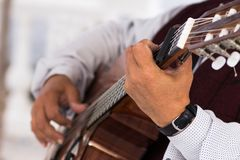 Close up of old hands playing an acoustic guitar. Royalty Free Stock Images