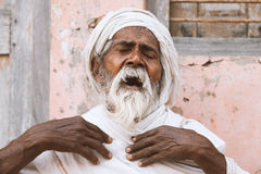 Close up of a old indian sadhu speak up sacred scriptures. Close up of a old indian sadhu sitting and speak up sacred texts with closed eyes near the temple royalty free stock photo