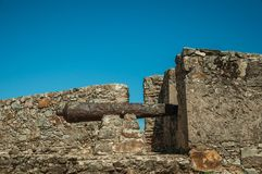 Iron cannon on the wall of stronghold next to the Marvao Castle. Close-up of old iron cannon on sunny day in the stone inner wall of stronghold next to the royalty free stock images