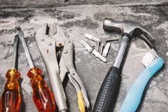 Close-up old joinery tools, Hammer, wrench, plastic anchors and drivers on dusty cement stock image