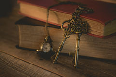 Close-up old key and pocket watch with stack of book on night li Royalty Free Stock Images