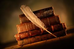 Old leather books with quill pen on wooden table. Close up of old leather books with quill pen on wooden table Royalty Free Stock Photo