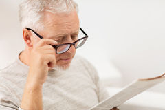 Close up of old man in glasses reading newspaper. Leisure, information, people, vision and mass media concept - close up of senior man in glasses reading Stock Image