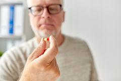 Close up of old man hand with pill. Age, medicine, healthcare and people concept - close up of senior man hand with pill Royalty Free Stock Photography