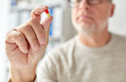 Close up of old man hand with pill. Age, medicine, healthcare and people concept - close up of senior man hand with pill Stock Photography