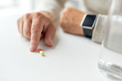 Close up of old man hand with pill and smart watch. Age, medicine, healthcare and people concept - close up of senior man hand with pill and smart watch Royalty Free Stock Images