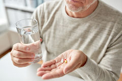 Close up of old man hands with pills and water. Age, medicine, healthcare and people concept - close up of senior man hands with pills and water glass at home Stock Photo