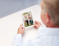 Close up of old man holding happy family photo. Oldness, memories, nostalgia and people concept - close up of old men holding and looking at happy family photo Royalty Free Stock Images