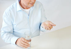 Close up of old man with pills and water glass Royalty Free Stock Images