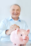 Close up of old man putting coin into piggybank. Savings, oldness, business, people and banking concept - close up of senior man putting coin into piggy bank Stock Photo