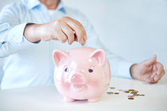 Close up of old man putting coins into piggybank. Savings, oldness, business, people and banking concept - close up of senior man hands putting coins into piggy Stock Image