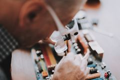 Close up. Old Man Repairing Motherboard from PC stock photography
