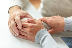 Close up of old man and young woman holding hands Stock Photo