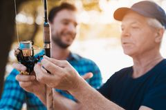 Close up. The old man inspects the fishing spinning spool. A man looks at the old man. Close up. The old men in a black T-shirt and black cap looks at the royalty free stock images