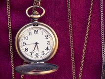 Old pocket watch and chains on the red floor stock photos