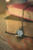 Close-up old pocket watch with stack of book on morning light in Royalty Free Stock Images