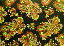 A close up of old printed paisley pattern. An elaborate shabby chic  paisley patterned background in yellow and black Royalty Free Stock Images