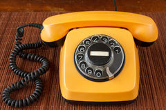Close up of an old, scratched orange rotary dial telephone Royalty Free Stock Photography