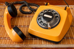 Close up of an old, scratched orange rotary dial telephone with the receiver left open on a bamboo mat Stock Photo