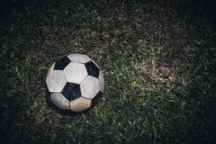 Old soccer ball or football lay on green grass for kick. Low key. Close up old soccer ball or football lay on green grass for kick and free form copy space. Dark stock image
