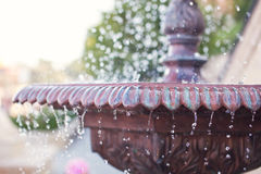 Close-up of an old stone fountain with dripping water on blurred background Royalty Free Stock Photo
