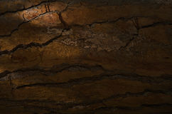 Close-up of old stony cracked wall in darkness Stock Photo
