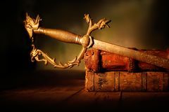 Old sword with leather books on wooden table royalty free stock image