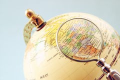 Close up of old vintage globe and magnifying glass Royalty Free Stock Photo
