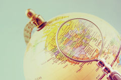 Close up of old vintage globe and magnifying glass. Stock Photo