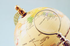Close up of old vintage globe and magnifying glass Stock Photography