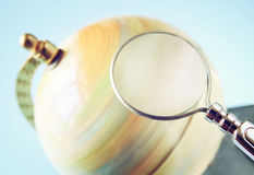 Close up of old vintage globe and magnifying glass Royalty Free Stock Images