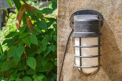 Close up old wall lamp on concrete wall with green natural in the background. Royalty Free Stock Images