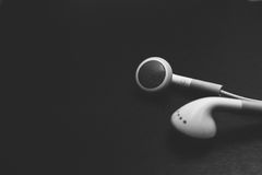 Close Up The Old White Earphone on Black Leather. Black and White Color Stock Images