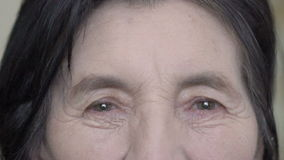Close up old woman's face, eyes, sincere looking on camera stock footage
