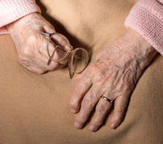 Close-up of old woman's hands with glasses Royalty Free Stock Photo