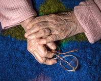 Close-up of old woman's hands with glasses Royalty Free Stock Images