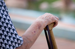 Wrinkled hand on wooden cane Stock Images