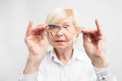 Close up of old woman is very attentive to details. She is looking to her glasses trying to find dirty spots there. She. Likes all things to stay clean. on royalty free stock image