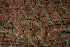 Close up of old wood fence panel  with plastic diamond pattern n. Etting. Harsh sunlight, strong shadows, could be used as horizontal or vertical abstract image Stock Photos