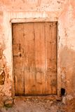 close up of an old wooden closed door in a wall of concrete, mud and stone in a closed abandoned house where nobody lives. royalty free stock photography